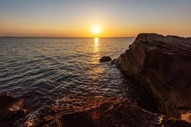 Colorido amanecer en la costa rocosa del mar