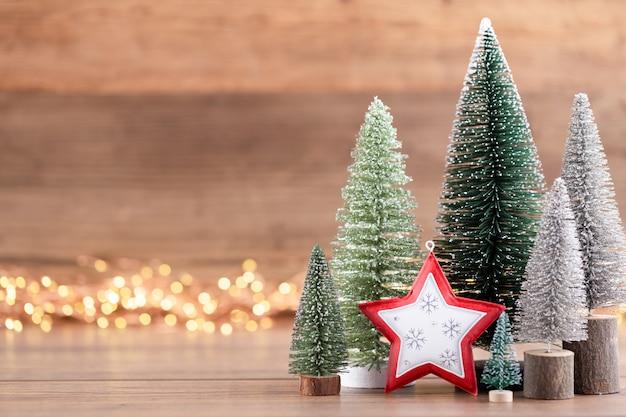 Colorido árbol de navidad sobre fondo de madera, bokeh. concepto de celebración navideña. tarjeta de felicitación.