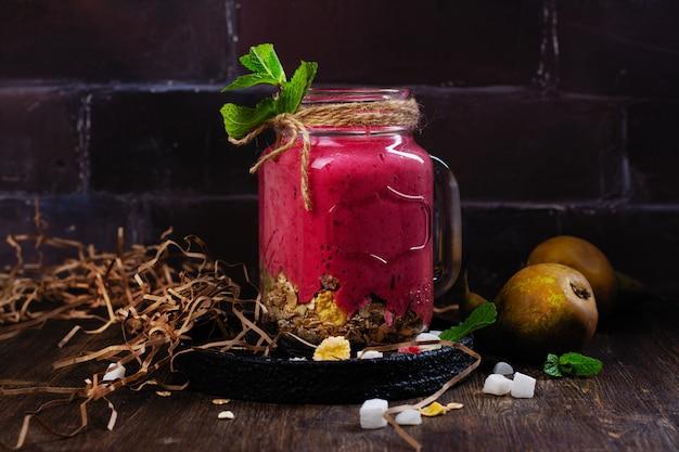 Colorido batido de verano de desintoxicación con bayas rojas, pera, granola y cubitos de coco secos