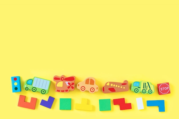 Colorido bebé niños juguetes de madera sobre fondo amarillo. desarrollando coloridos bloques, autos y aviones. vista superior. endecha plana. copiar espacio para texto