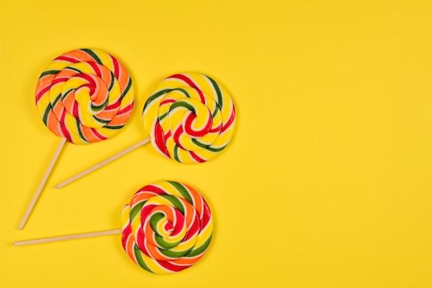 Colorido caramelo sobre un fondo amarillo. pirulí. vista superior. copia espacio