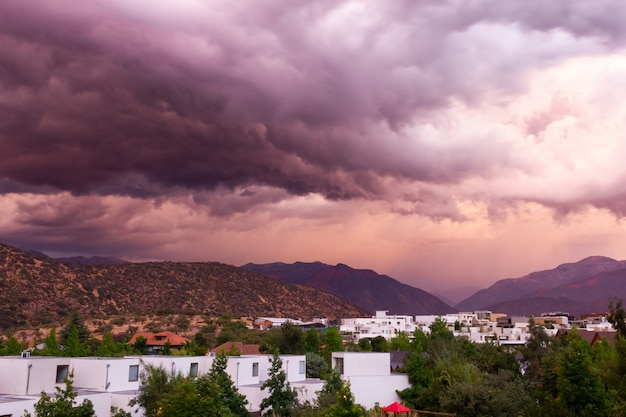 Colorido cielo dramático sobre una zona residencial rodeada de montañas al atardecer concepto de amenaza de tormenta