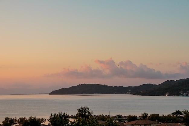 Colorido cielo de vainilla bajo el mar de plata en calma y montañas rocosas al amanecer