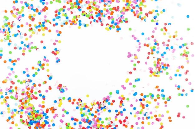 Colorido confeti surtido con serpentina sobre fondo blanco.