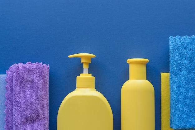 Colorido conjunto de limpieza para diferentes superficies sobre fondo azul. concepto de limpieza con suministros. botellas de plástico, envases de detergente, paño de microfibra, esponja. trapo y detergente, copia de espacio