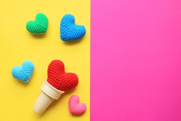 Colorido de corazón de ganchillo hecho a mano en taza de galleta sobre fondo amarillo y rosa con copyspace para el día de san valentín