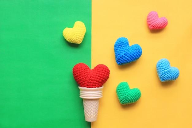 Colorido del corazón de ganchillo hecho a mano en una taza de waffle sobre fondo amarillo y verde para el día de san valentín