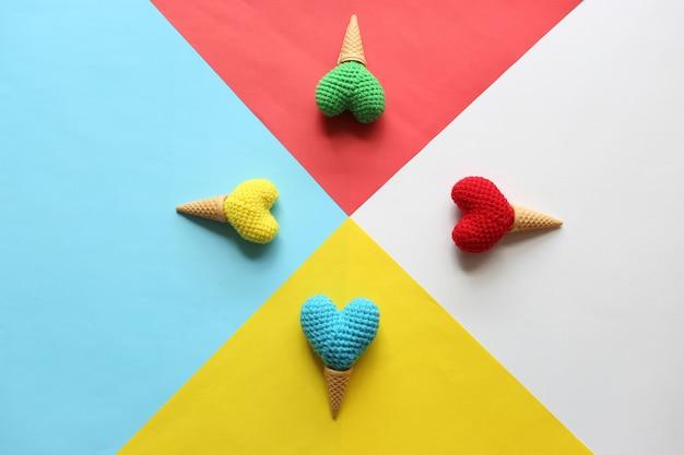 Colorido de corazón de ganchillo hecho a mano en taza de waffle sobre fondo colorido para el día de san valentín