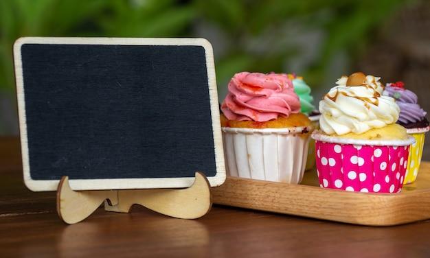 Colorido de cupcake casero en bandeja de madera con pizarra vacía