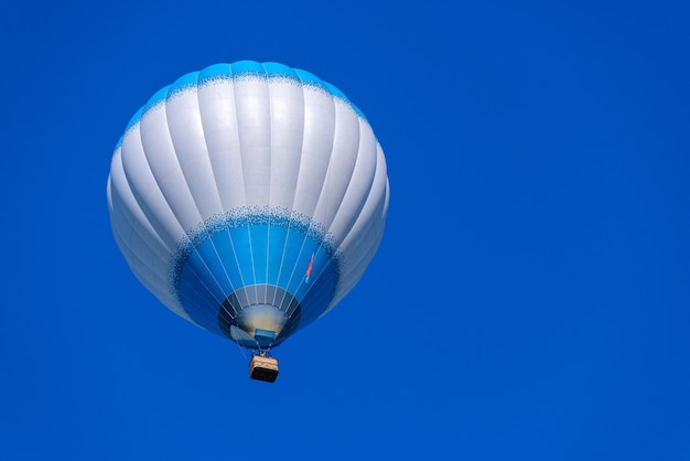 Colorido globo de aire caliente volando sobre un fondo de cielo azul