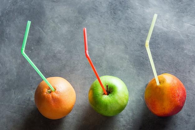Colorido maduro frutas orgánicas mango pomelo manzana con pajitas jugos frescos salud detox