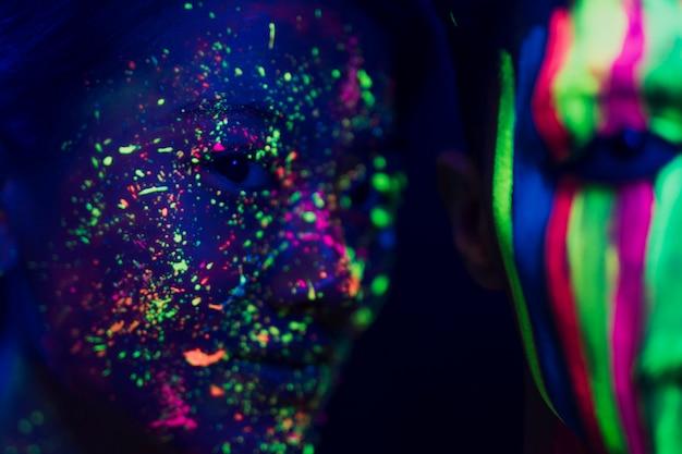 Colorido maquillaje fluorescente en cara de mujer y hombre