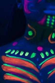 Colorido maquillaje fluorescente en el cuerpo de la mujer