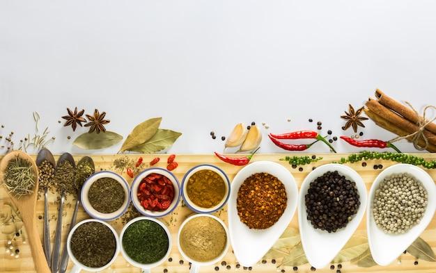 Colorido de muchas especias y hierbas en blanco pequeño tazón y cucharas puesto en tablón de madera
