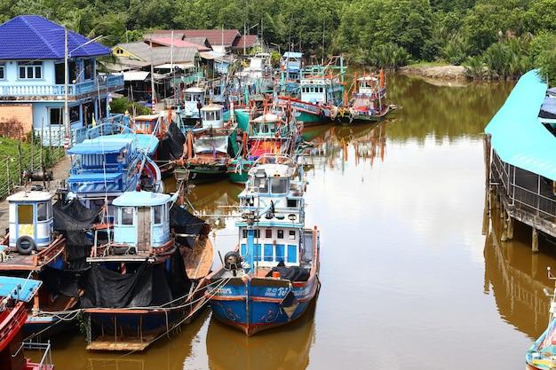 Colorido muelle de barco de pesca en el muelle del pueblo en el río canal