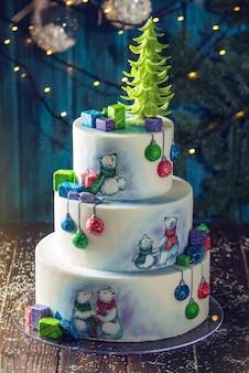 Colorido pastel navideño de tres niveles decorado con dibujos de ositos de peluche, cajas de regalo y una copa de árbol verde