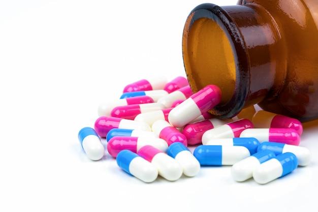 Colorido de píldoras cápsulas antibióticas con botella de vidrio ámbar
