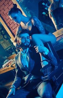 Colorido retrato de hermosa pareja: hombre brutal en traje elegante y chica sexy con un tatuaje con lencería en peluquería