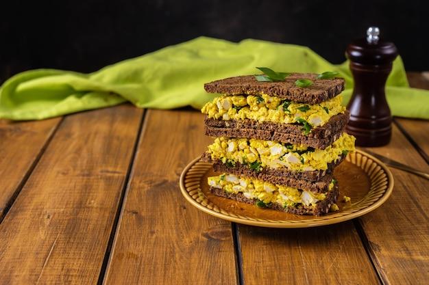 Colorido sandwich de hamburguesa vegana con ensalada de huevo vegano