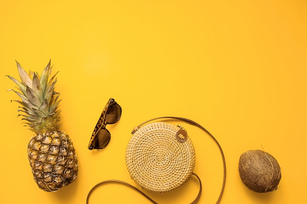 Colorido traje de moda femenina de verano, plano, con bolsa de bambú, gafas de sol, coco, piña.
