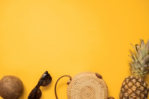 Colorido traje de moda femenina de verano, plano, con bolsa de bambú y gafas de sol.