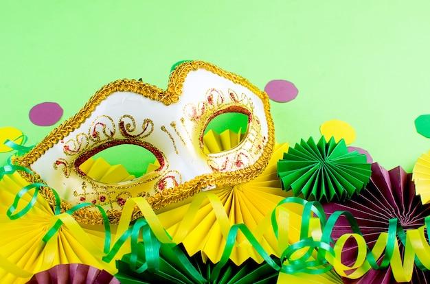 Coloridos abanicos de carnaval y máscara en mesa amarilla