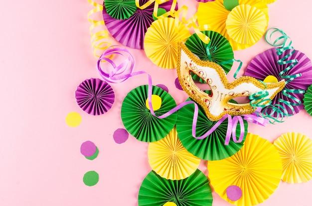 Coloridos abanicos de carnaval y máscara en mesa rosa