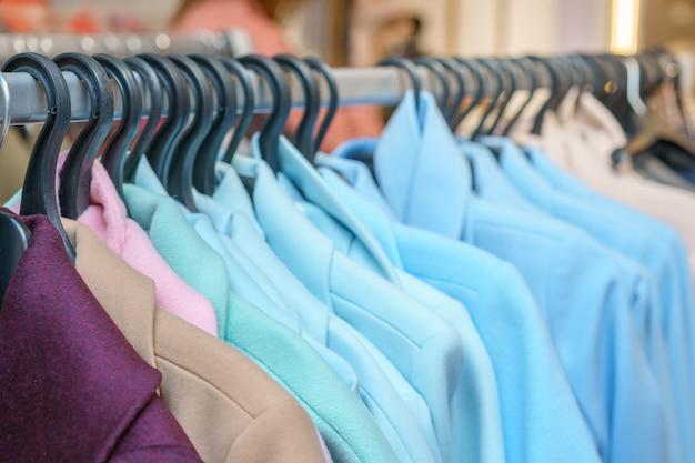 Coloridos abrigos colgados en perchas en la tienda