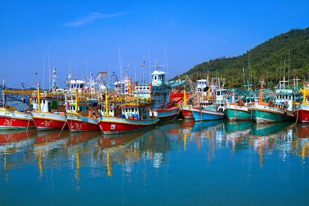Coloridos barcos de pesca están estacionados en el mar tropical en tailandia.