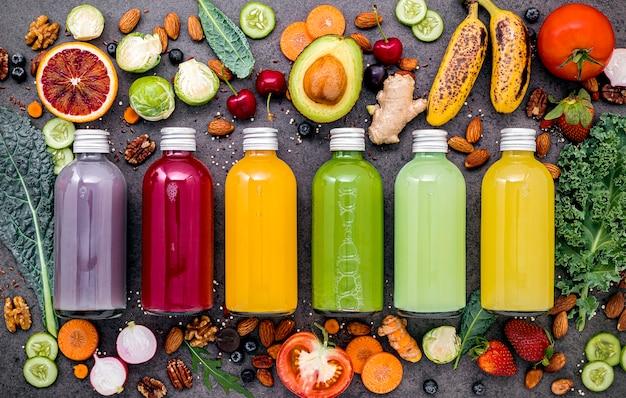Coloridos batidos y jugos saludables en botellas con frutas tropicales frescas y superalimentos en piedra oscura