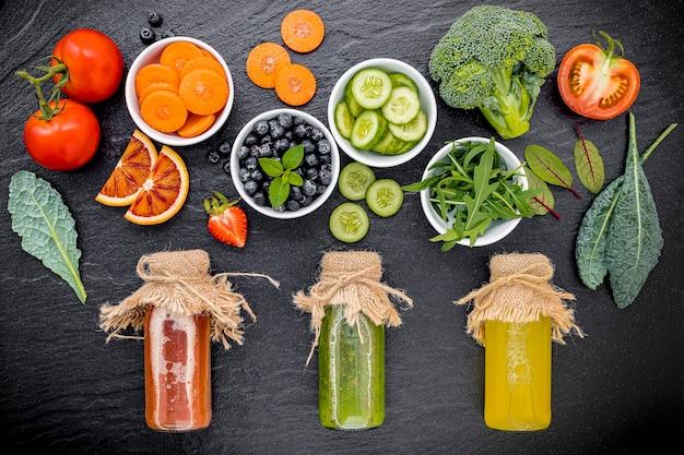 Coloridos batidos saludables y jugos en botellas con fruta tropical fresca sobre fondo de piedra oscura.