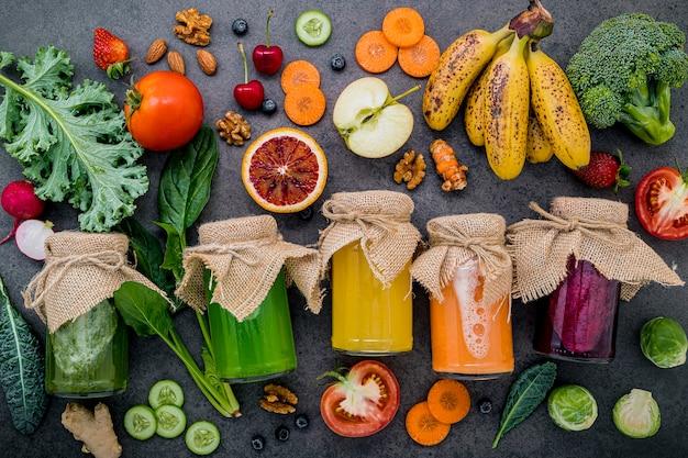 Coloridos batidos saludables y jugos en botellas con frutas tropicales frescas y superalimentos sobre fondo de piedra oscura con espacio de copia.