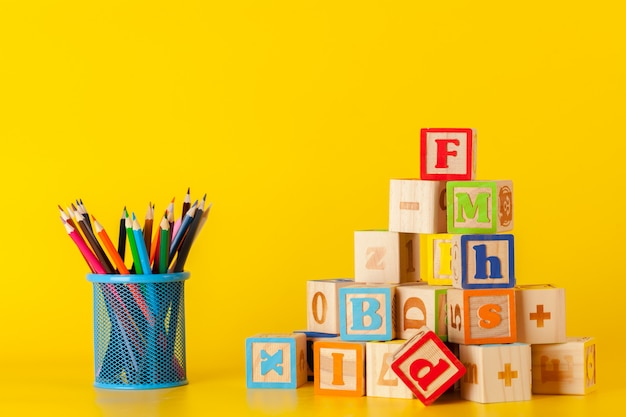 Coloridos bloques de madera y taza con lápices de colores.