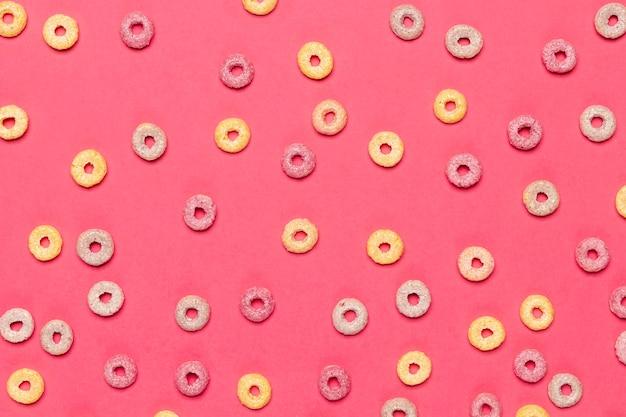 Coloridos bucles de fruta de cereales sobre fondo rosa