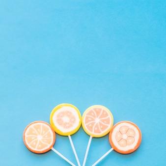 Coloridos caramelos redondos de lollipop dispuestos sobre el fondo azul