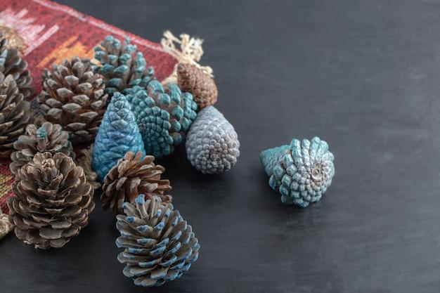 Coloridos conos de roble sobre un trozo de alfombra étnica de patrón rojo
