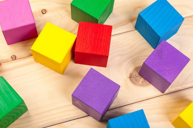 Coloridos cubos de madera en mesa de madera