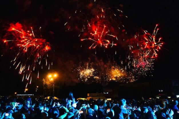 Coloridos fuegos artificiales en el cielo nocturno y multitud en concierto en kineshma