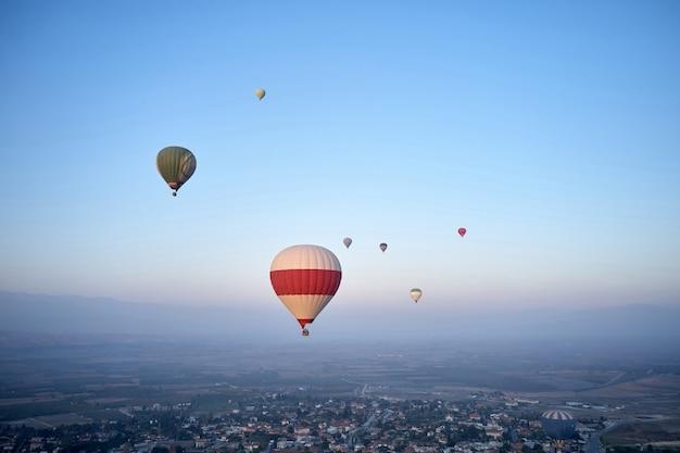 Coloridos globos aerostáticos volando en el cielo de la mañana