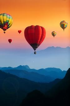 Coloridos globos aerostáticos volando sobre montañas azules