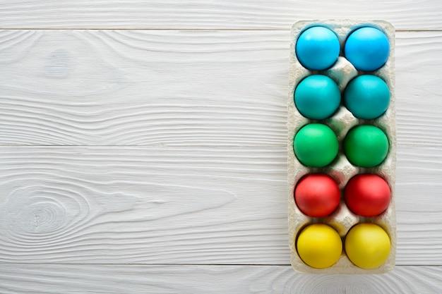 Coloridos huevos de pascua en una bandeja sobre una mesa de madera blanca