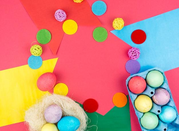 Coloridos huevos de pascua en caja y en nido sobre mesa