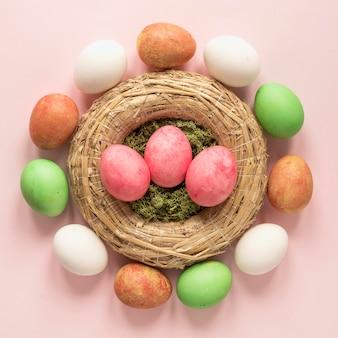 Coloridos huevos de pascua en canasta de heno