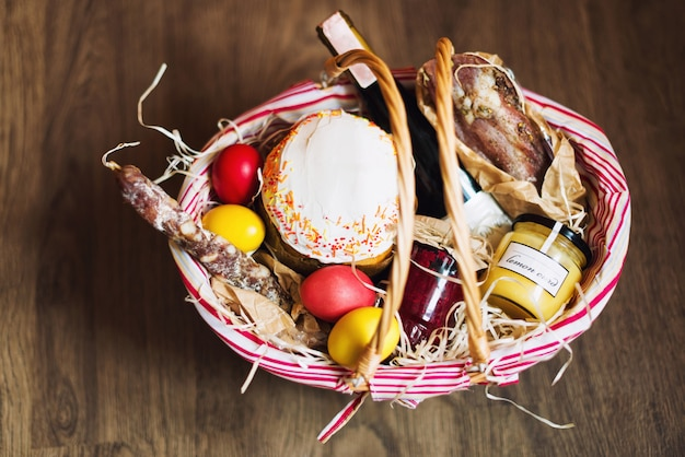 Coloridos huevos de pascua en una canasta con pastel, vino tinto, jamón o salchicha seca y seca