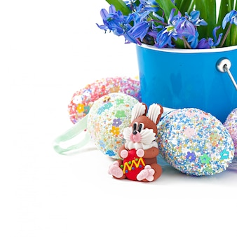 Coloridos huevos de pascua en una cesta en un blanco
