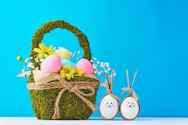 Coloridos huevos de pascua en cesta con decoraciones de flores sobre un fondo azul.
