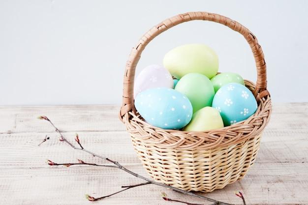 Coloridos huevos de pascua en cesta en madera