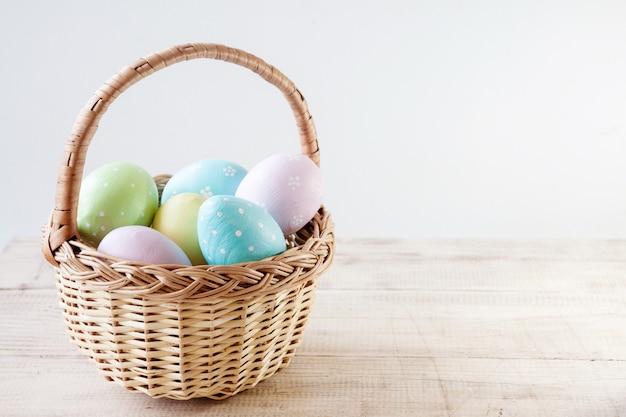 Coloridos huevos de pascua en cesta en mesa de madera.