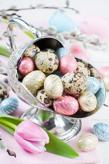 Coloridos huevos de pascua de chocolate en florero de metal.