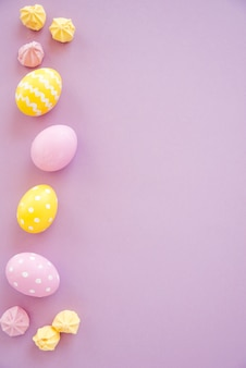 Coloridos huevos de pascua con dulces en mesa púrpura